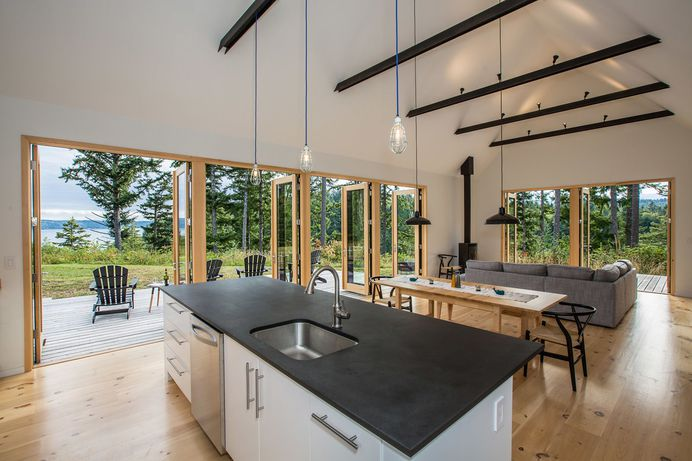 Kitchen, Granite Counter, Pendant Lighting, Undermount Sink, Light Hardwood Floor, White Cabinet, and Dishwasher Clean, white, and warm interiors are punctuated by darker accents. Photo 109 of 2509 in Best Kitchen Photos from The Coyle