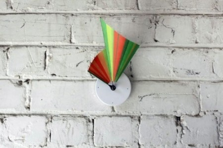 This is a clock made from a printed piece of tyvek. The side edges of the tyvek are the hands the clock. As the time clicks away, the clock