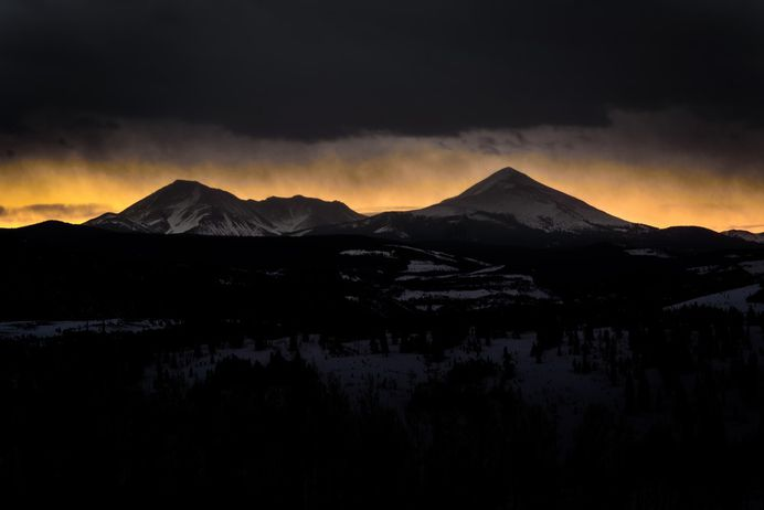 Silhouettes of snow-covered mountains against the orange sunset sky in Silverthorne