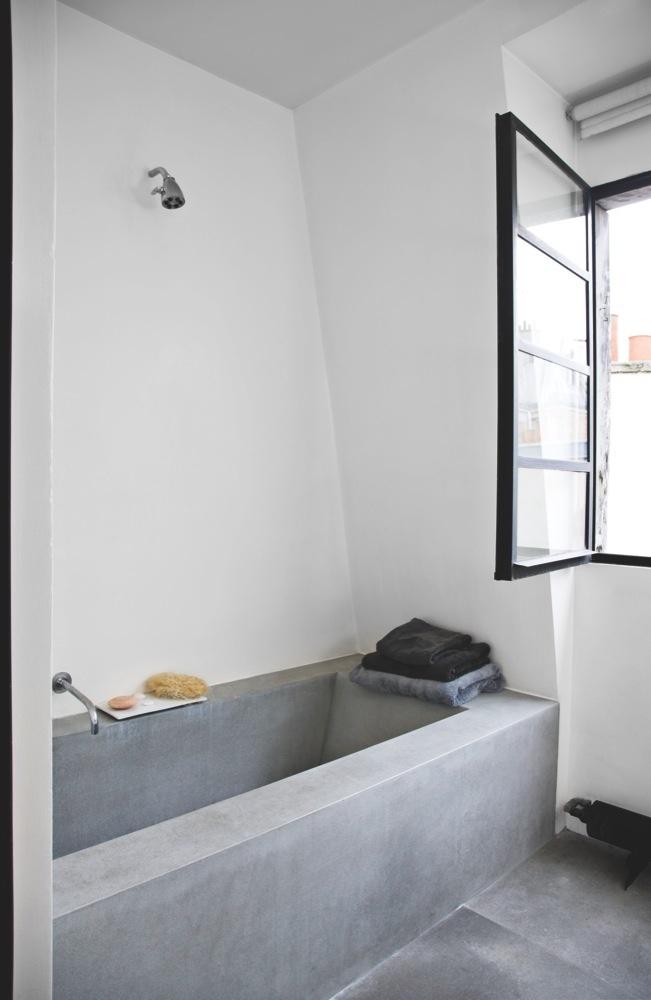 Bathroom with concrete bathtub and floor Photo