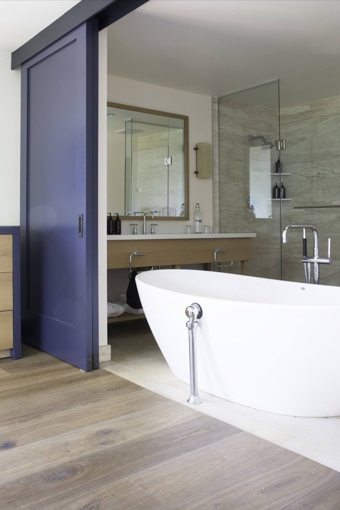 The designers used a neutral palette with durable, sealed stone in the bathrooms. Most rooms have large soaking tubs; here, the large ensuite bath can be hidden from the room via blue-painted sliding doors.