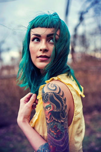 Portrait of young woman with blue hair and tattoos looking up over her shoulder. #ink #tattoo #portrait